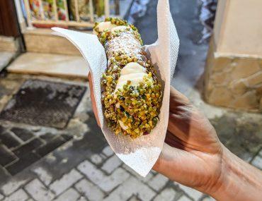 Syrakuzy - tradycyjne sycylijskie cannolo z ricottą maczane w kruszonych pistacjach
