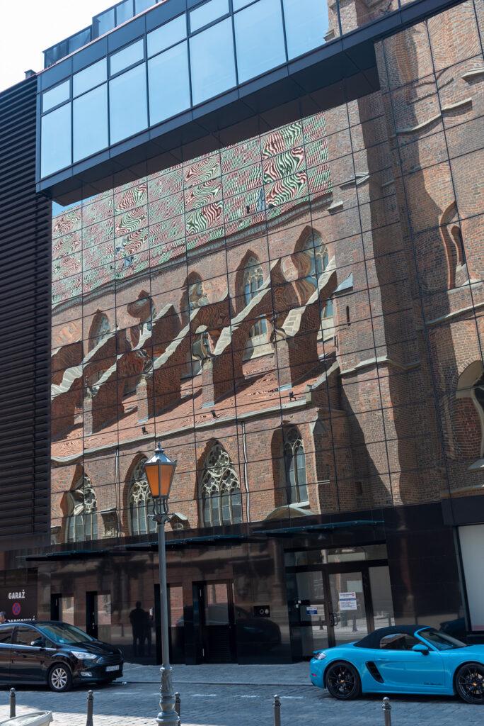Katedra św. Marii Magdaleny odbita w budynku hotelu Qubus